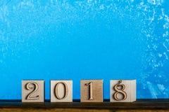 Datum 2018 för nytt år Kuber av naturligt trä Djupfrysta fönsterblåttlodisar Royaltyfri Bild