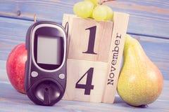 Datum am 14. November als Symbol des Weltdiabetestages, Glukosemeter für messendes Zuckergehalt und Früchte Stockbild