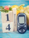 Datum am 14. November als Symbol des Weltdiabetestages, Glukosemeter für messendes Zuckergehalt und Früchte mit Gemüse Lizenzfreies Stockfoto