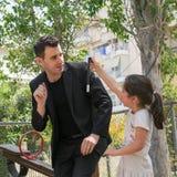 Datum: 17/5/2015 Standort: Park in Athen Griechenland Zaubertrickstab fällt unten und bremst plötzlich, wenn das Kind ihn nimmt Stockbild