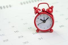 Datum und Zeitanzeigen- oder -fristenkonzept, kleiner roter Wecker auf weißem sauberem Kalender mit der Anzahl des Tages, unten z stockfotos