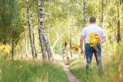 Datumet i mannen för skog A med blommor väntar hans baksida på en kvinna på en cykel royaltyfri bild