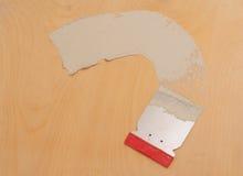 The daub of plaster and the scraper. Scraper and plaster daubed on the veneer sheet Royalty Free Stock Photo