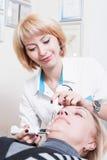 Dauerhafter Kosmetiker der schönen jungen blonden Frau in einer weißen Robe Stockfoto