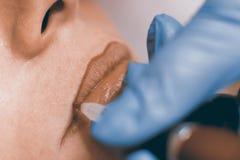 Dauerhaftes bilden Cosmetologist, der dauerhaftes Make-up auf Li anwendet stockfoto