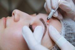 Dauerhaftes Make-up f?r Augenbrauen Microblading-Braue Kosmetiker, der die Augenbraue t?towiert f?r weibliches Gesicht tut Sch?ne lizenzfreie stockfotografie