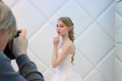 DAUERWELLE, RUSSLAND - 12. FEBRUAR 2017: Fotograf schießt blonde Braut herein Lizenzfreie Stockfotografie