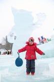 DAUERWELLE, RUSSLAND - 6. JANUAR 2014: Kleines Mädchen nahe Skulptur Stockbild