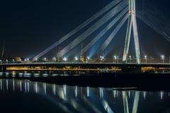 Daugava Cable-permanecido en la noche, Riga, Letonia del puente y del río Imagenes de archivo