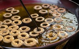 Daugh roll of donut dessert on boil. Wood stick making donut with ring daugh on hot oil stock image