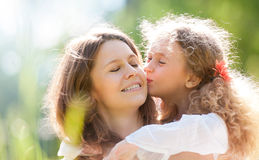 Daugher kissing her mother Stock Photography