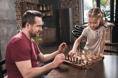 Preschooler Daughter arranging chess pieces for game. With her father stock image