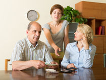 Daughter asking parents for money Stock Photography