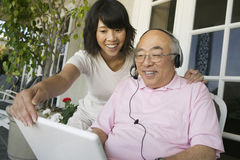 Daughter Assisting Father In Using Laptop At Porch Stock Image