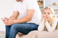Daughter and busy father sitting on the sofa Stock Photos