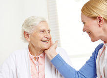 Daughter caressing happy senior. Mother with her hand over her cheek Royalty Free Stock Image