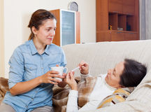 Daughter caring for sick mature mother Stock Photo