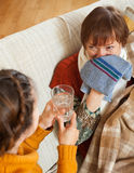 Daughter caring for sick mature mother has cough. In living room. Focus on mother Stock Photo