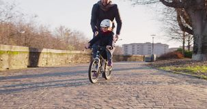 Daughter child girl learning riding bycicle with dad teaching in city.Growing,childhood,active safety family.Sidewalk stock footage