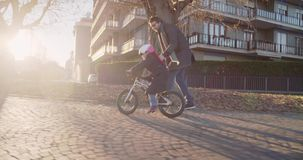 Daughter child girl learning riding bycicle with dad teaching in city.Growing,childhood,active safety family.Sidewalk. Urban outdoor.Warm sunset cold weather stock video