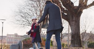 Daughter child girl learning segway riding with dad teaching in city.Modern future transport technology.Active safety stock video footage