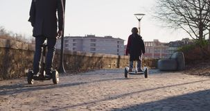Daughter child girl riding segway with her dad in city.Modern future transport technology.Active Family.Park sidewalk stock footage