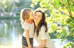 Daughter child kissing happy mother in summer Royalty Free Stock Photo