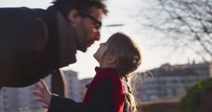 Daughter child kissing her dad. Modern future transport technology.Active Family.Park sidewalk urban outdoor.Warm sunset stock footage