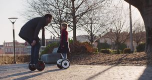 Daughter child kissing her dad riding segway hoverboard. Modern future transport technology.Active Family.Park sidewalk. Urban outdoor.Warm sunset cold weather stock footage