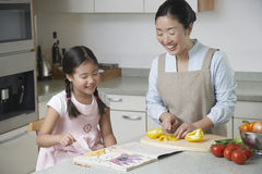 Daughter Coloring And Mother Cutting Bell Pepper In Kitchen Stock Photo