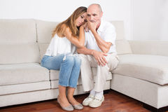 Daughter comforting her father. Elderly men sitting with a younger women on the sofa royalty free stock image