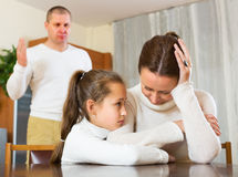 Daughter comforting sad mother. In livingroom and angry father Royalty Free Stock Photography