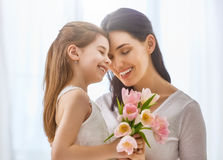 Daughter congratulates mom. Happy mother`s day! Child daughter congratulates mom and gives her flowers tulips. Mum and girl smiling and hugging. Family holiday Royalty Free Stock Photos