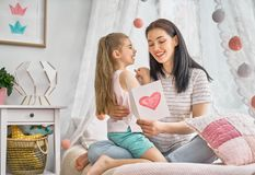 Daughter is congratulating mom Stock Images