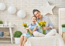 Daughter congratulating mom. Happy women`s day! Child daughter is congratulating mom and giving her flowers tulips. Mum and girl smiling and hugging. Family Royalty Free Stock Image