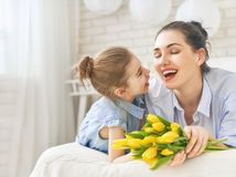 Daughter congratulating mom Stock Images