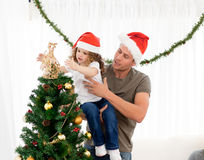 Daughter decorating the christmas tree Royalty Free Stock Photos