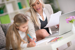 Daughter doing homework with mom's help royalty free stock photo