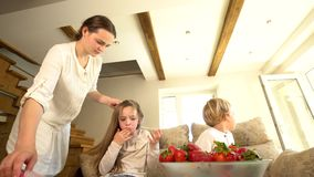 Daughter eats strawberry while mother comb hair and brother. Dish of berries stock footage