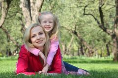 Daughter embraces mother lying on grass Stock Photo