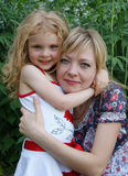 Daughter embraces mother in the park. The daughter embraces mum against green plants in the park. 4-5 years old girl Stock Image