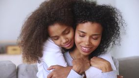 Daughter embracing mother closed eyes enjoy moment of tenderness closeup. Close up view attractive afro biracial mother and grown-up pre-teen daughter or stock video