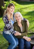 Daughter Embracing Mother Sitting On Chair At Stock Image