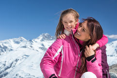 Daughter embracing mother in snow stock photography
