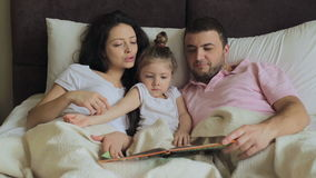 Daughter with family reading a book in bed stock video footage