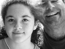 Daughter and Father B&W. A young girl smiling with her father hugging her. Black and White stock photo
