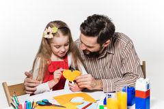 The daughter and father carving out paper applications Royalty Free Stock Image