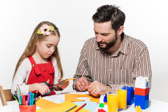 The daughter and father carving out paper applications Stock Image