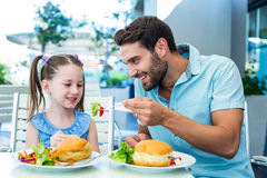 Daughter and father eating at the restaurant Royalty Free Stock Image