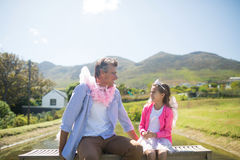 Daughter and father in fairy costume interacting with each other. At garden on a sunny day Royalty Free Stock Photos